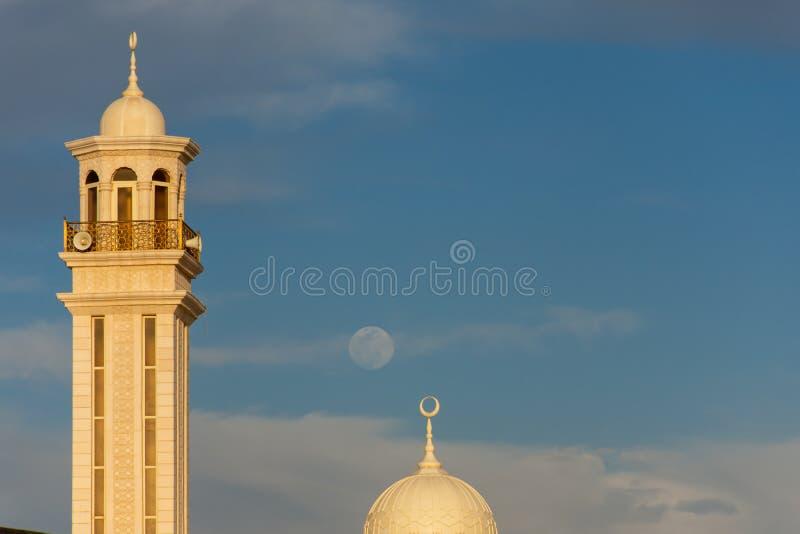 Rzadka dzienna księżyc w pełni z niebieskim niebem za minaretami lokalny meczet w Zjednoczone Emiraty Arabskie fotografia royalty free