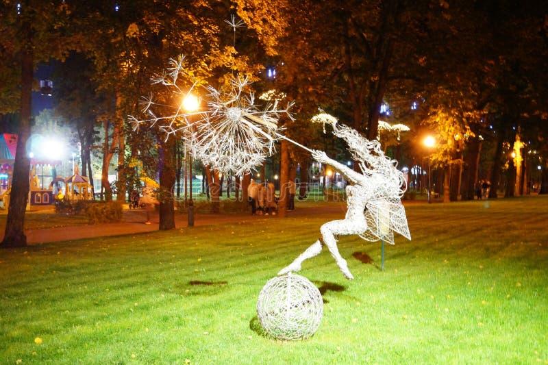 Rzeźba latająca czarodziejka z parasolem w miasto parku w wieczór zdjęcie stock