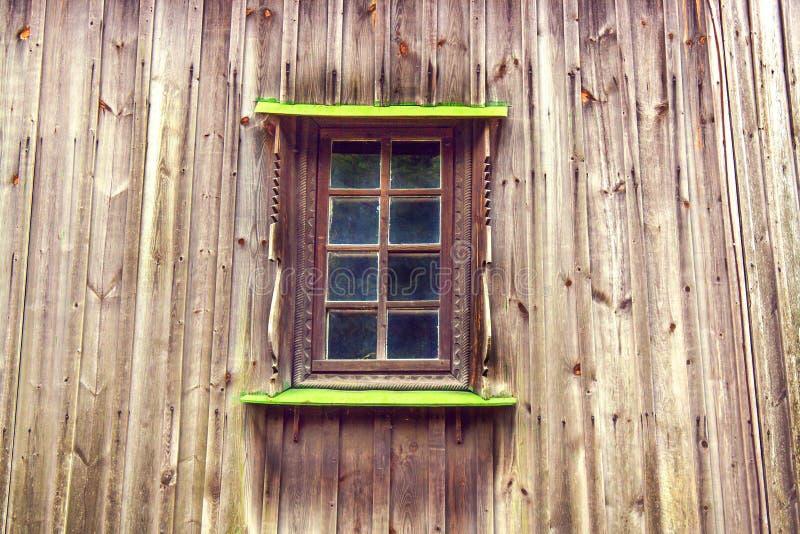 Rzeźbiący okno w starym drewnianym domu od desek i rama obraz stock