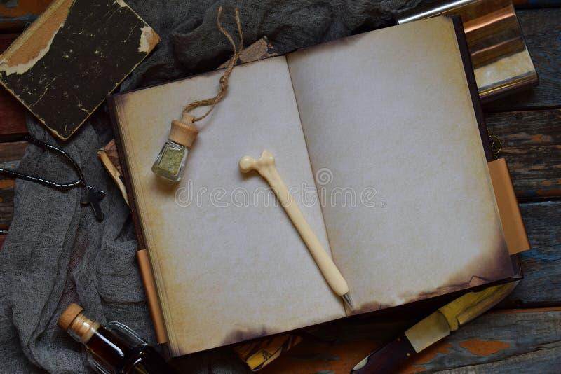 Rzecz myśliwy dla zła, demony, wampiry i żywi trupy, - stary notatnik, książka z czarami, nóż, kolba święta woda, pióro kość zdjęcia royalty free