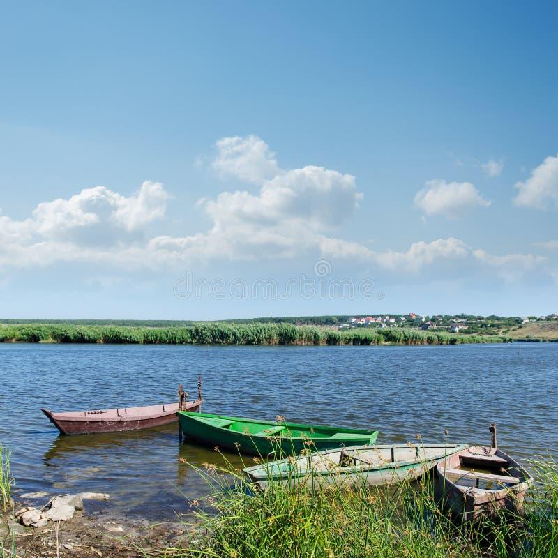 Download Rzeczne I Stare łodzie Pod Chmurnym Niebem Zdjęcie Stock - Obraz złożonej z odzwierciedlający, wybrzeże: 28953020
