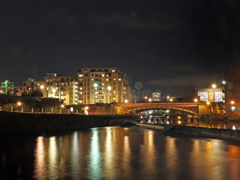 rzeczny Aire w Leeds przy nocą pokazuje budynki z obu stron korona punktu mostu i jazu z jaskrawymi światłami odbijającymi zdjęcie royalty free