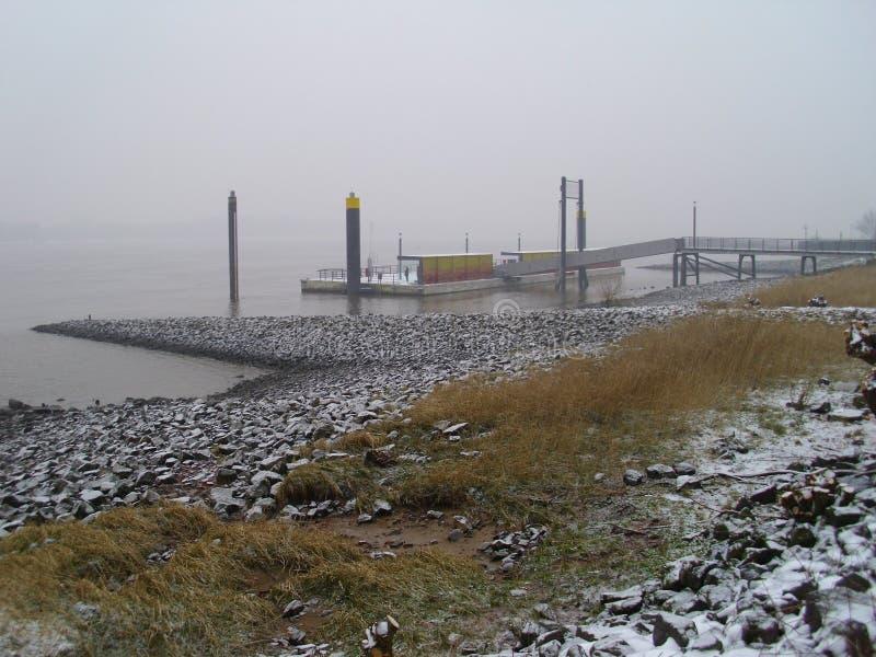 Rzeczny Elbe blisko Hamburg, ląduje most prom w zimie i mgle, także well widoczny obraz royalty free