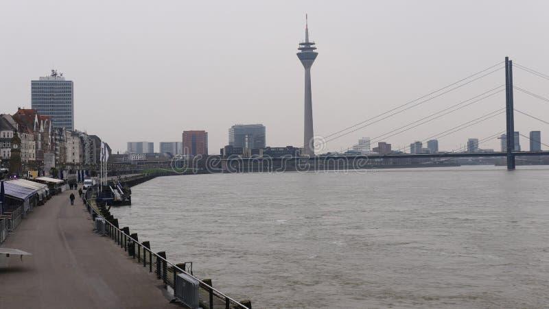 Rzeczny Rhine przy Dusseldorf Niemcy, widok brzeg deptak w tła Oberkasseler moście i wierza, zdjęcie royalty free