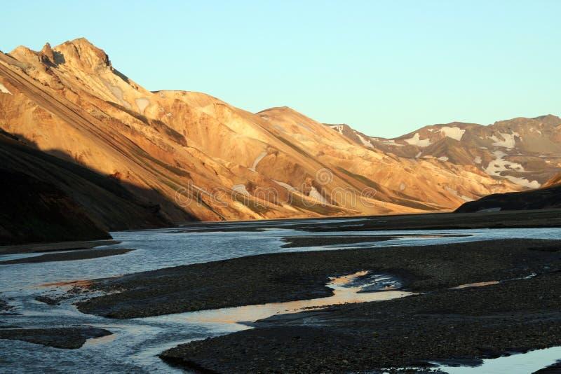 Rzeczny spływanie między czerwonymi i pomarańczowymi wzgórzami Kerlingarfjoll obrazy stock