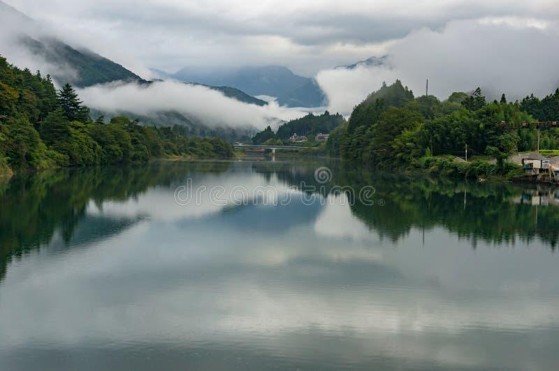 Rzeczny widoku krajobraz z lasów bankami i niskimi chmurami zdjęcia royalty free
