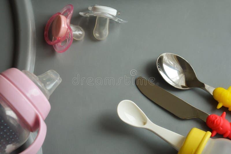 Rzeczy dla karmić dziecka butelki, sutki, łyżki i nóż na popielatym stole, obraz stock