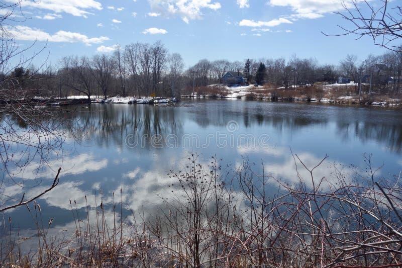 Rzeka, chmury, niebieskie niebo, nadzy drzewa, śnieżni banki, odbicia obraz stock