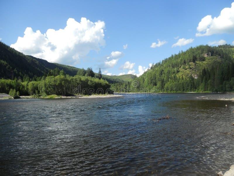 Rzeka i góry przeciw chmurom i niebieskiemu niebu obrazy royalty free