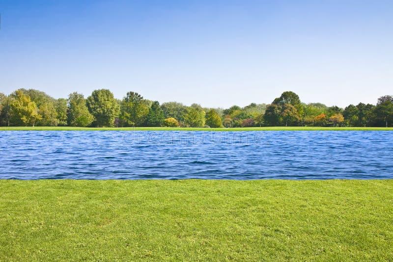 Rzeka płynie cicho na płaskiej ziemi z skoszonym gazonem i drzewami zdjęcia royalty free