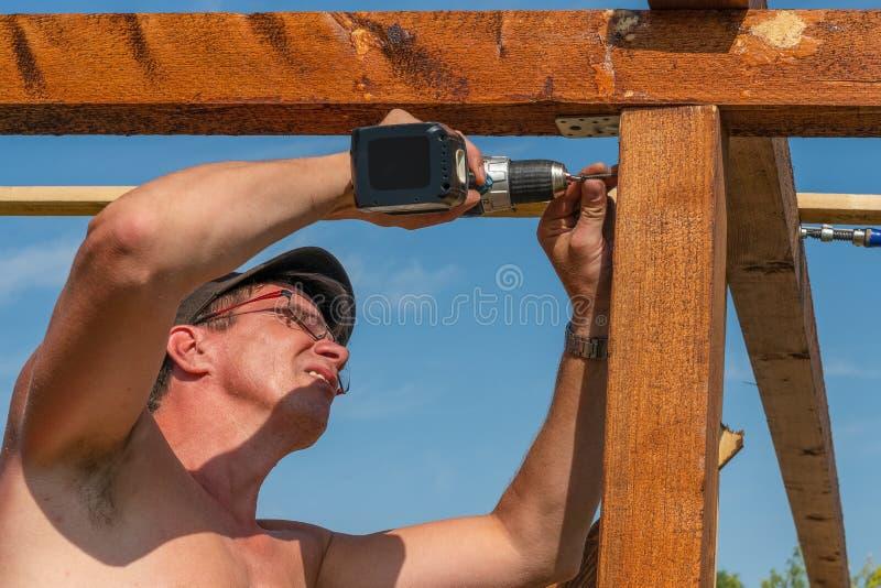 Rzemieślnik budowy lata dom z cordless śrubokrętem zdjęcia royalty free
