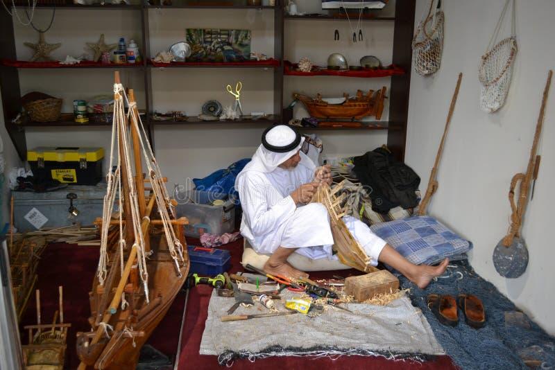 Rzemieślnik od Katar w tradycyjnym odziewa tworzyć handmade drewnianego modela statki zdjęcia stock