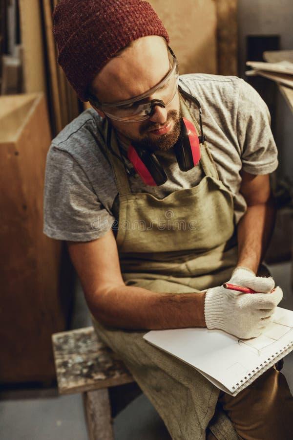 Rzemieślnik patrzeje daleko od z sketchbook zdjęcie royalty free