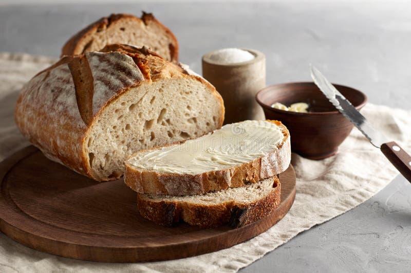 Rzemieślnik pokrajać grzanka chleb z masłem i cukierem na drewnianej tnącej desce Prosty śniadanie na popielatym betonowym tle obrazy stock