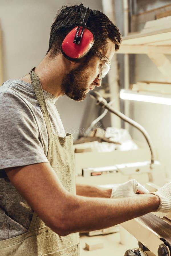 Rzemieślnik poleruje drewnianą część w słuchawki obraz royalty free