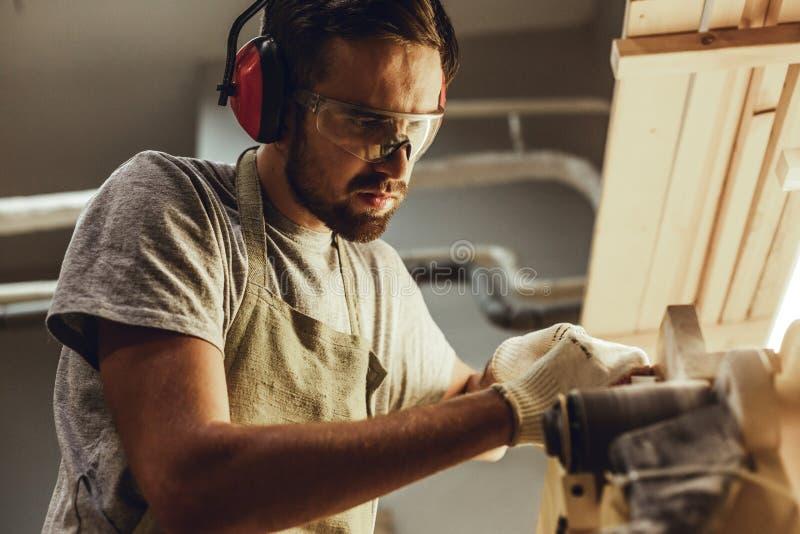Rzemieślnik pracuje z drewnem na pasowym sander zdjęcia stock