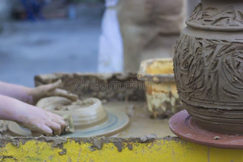 Rzemieślnik wręcza robić glinianemu garnkowi na ceramicznym kole zdjęcia stock