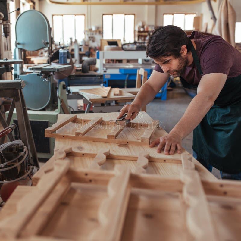 Rzemieślnik zręcznie sanding drewno podczas gdy pracujący w jego ciesielki studiu fotografia stock