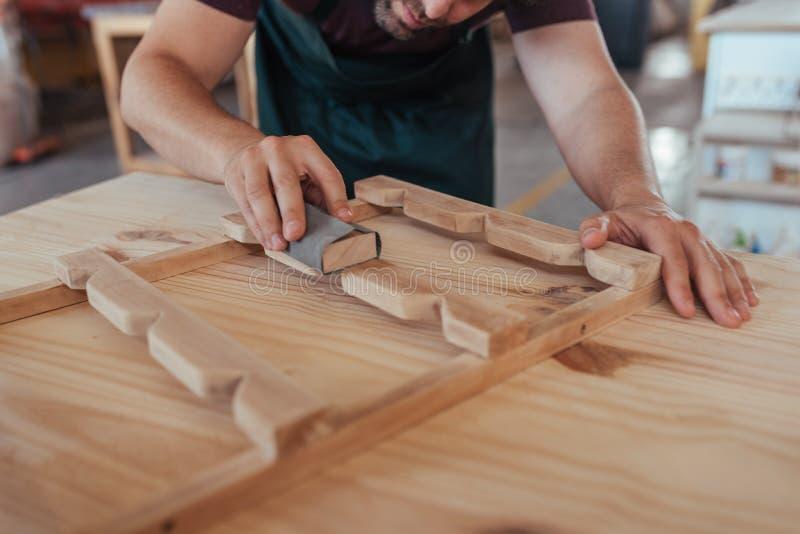 Rzemieślnik zręcznie sanding kawałek drewno w jego warsztacie fotografia stock