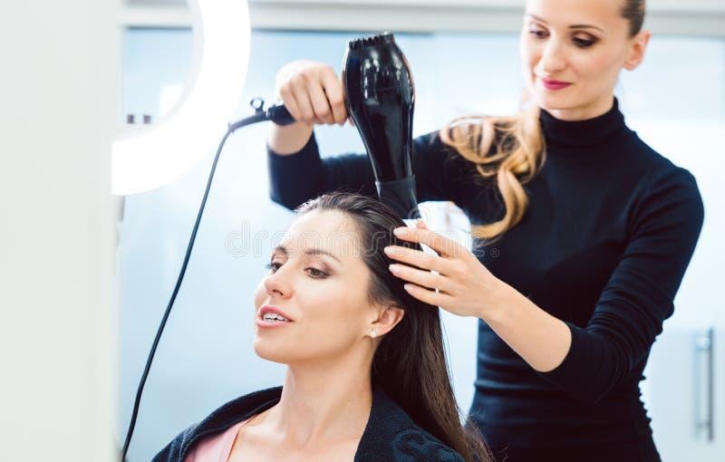 Rzemieślnika fryzjera ciosu suszarniczy włosy klient fotografia stock