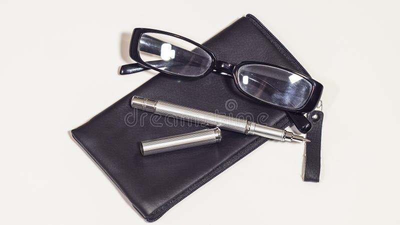 Rzemienna czerni pokrywa, biznesowi szkła i metalu pióro, fotografia stock