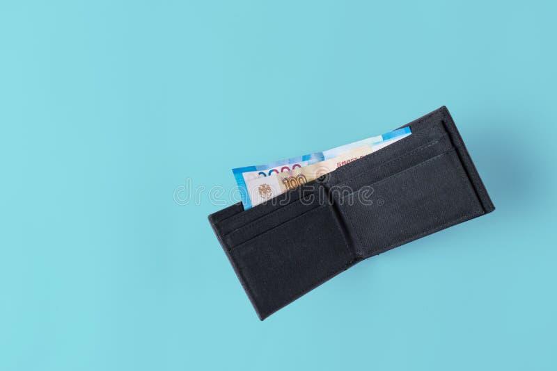 Rzemienna portfel kiesa z pieniądze na błękitnym tle zdjęcia stock