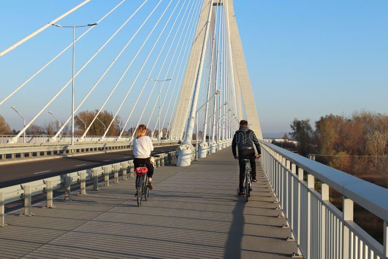 Rzeszow, Polônia - 9 9 2018: Um indivíduo com as bicicletas de montada de uma menina em uma ponte da estrada da suspensão através imagem de stock