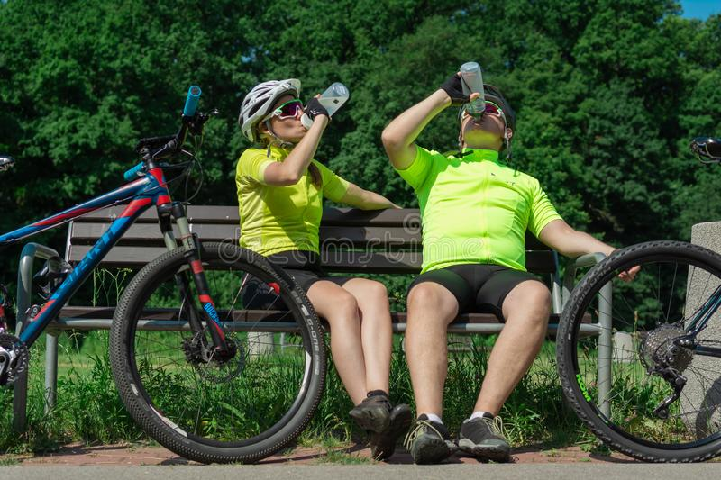 Rzeszow, Poland - Jun 23.2019 A young guy and a young girl are resting after a bike ride, drinking water, sitting on a bench. stock photography