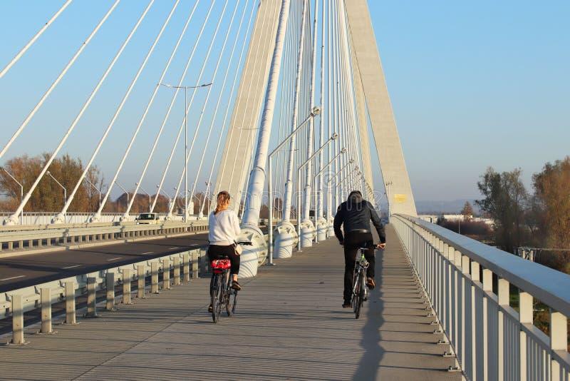 Rzeszow Polen - 9 9 2018: En grabb med en flicka som rider cyklar på en upphängningvägbro över den Wislok floden på ett soligt, c royaltyfri foto
