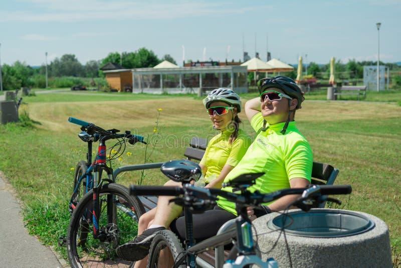 Rzeszow, Polonia - 23 de junio 2019 un individuo joven y una chica joven están descansando después de un paseo de la bici, agua p imagen de archivo libre de regalías