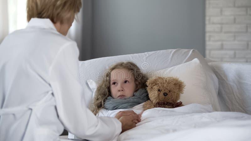 ?rztin, die eigenh?ndig krankes M?dchen h?lt und zu Hause mit ihr, Behandlung spricht stockfotografie