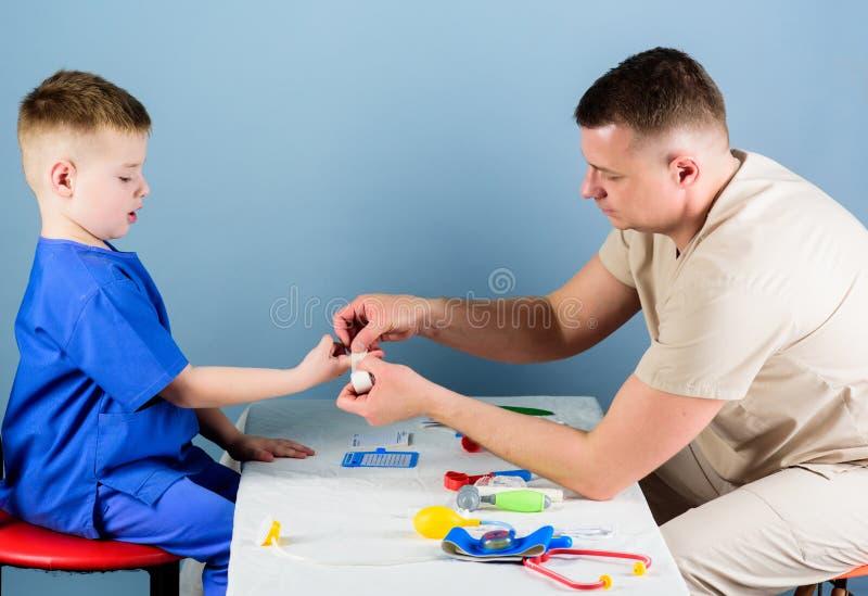 ?rztliche Bem?hung Manndoktor sitzen medizinische Werkzeuge der Tabelle wenig Jungenpatienten ?berpr?fend : Str?flinge und Arme stockbild