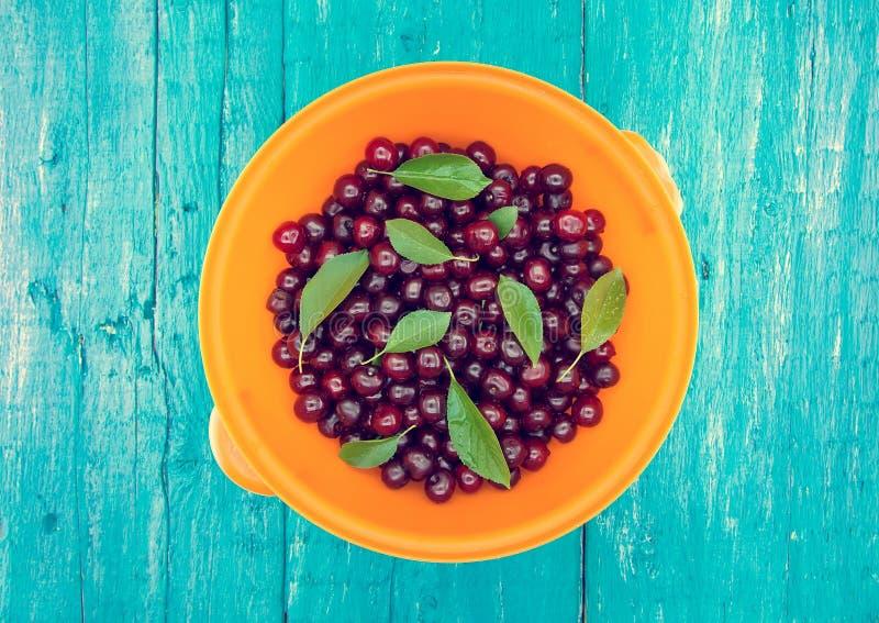 Rzuca kulą z świeżymi słodkimi wiśniami na błękitnym nieociosanym drewnianym tle fotografia royalty free