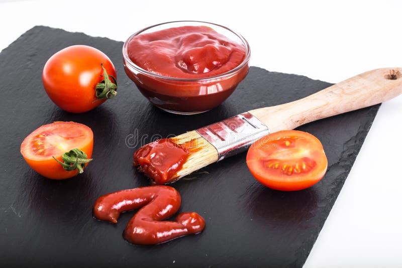 Rzuca kulą z ketchupem, pomidorami i muśnięciem na czerń kamienia tle, obraz royalty free