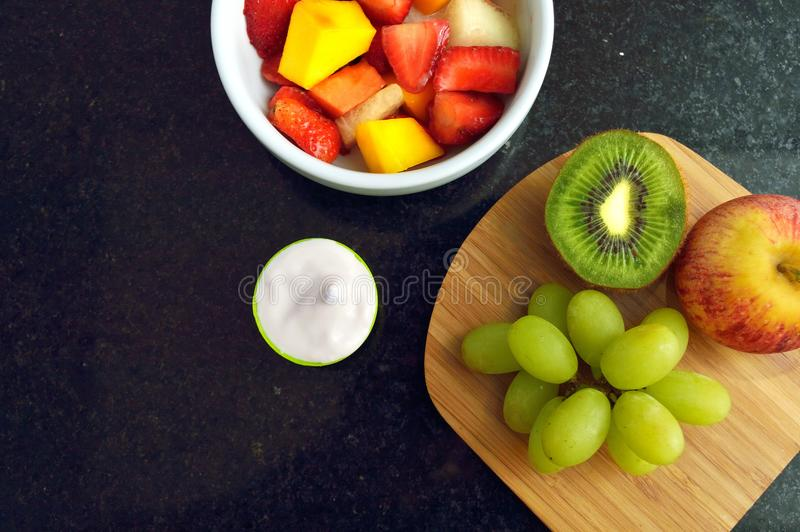 Rzuca kulą z Owocową sałatką i niektóre jogurtem na granitowym countertop widzieć od bezpośrednio above obrazy stock