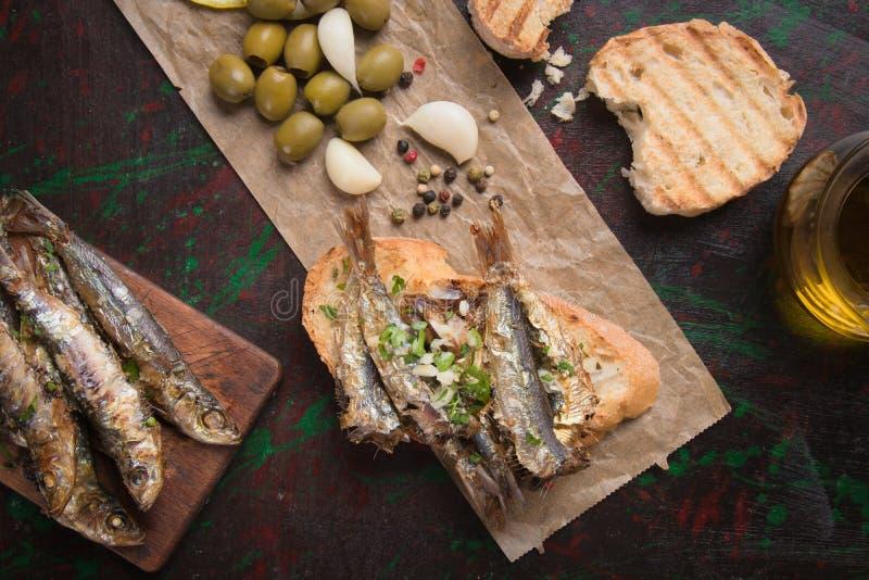 Sándwich de pescado sardino con ajo y aceite de oliva imagenes de archivo
