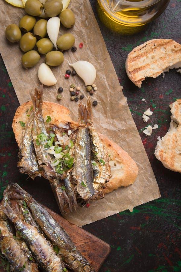 Sándwich de pescado sardino con ajo y aceite de oliva imagen de archivo