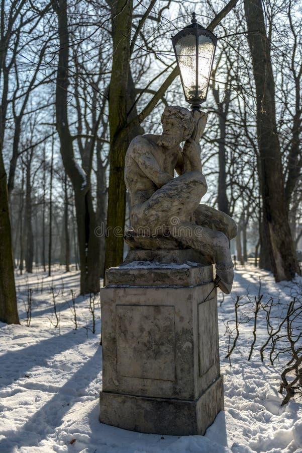 Sátiro de assento que apoia a lanterna do parque em Varsóvia, Polônia imagem de stock