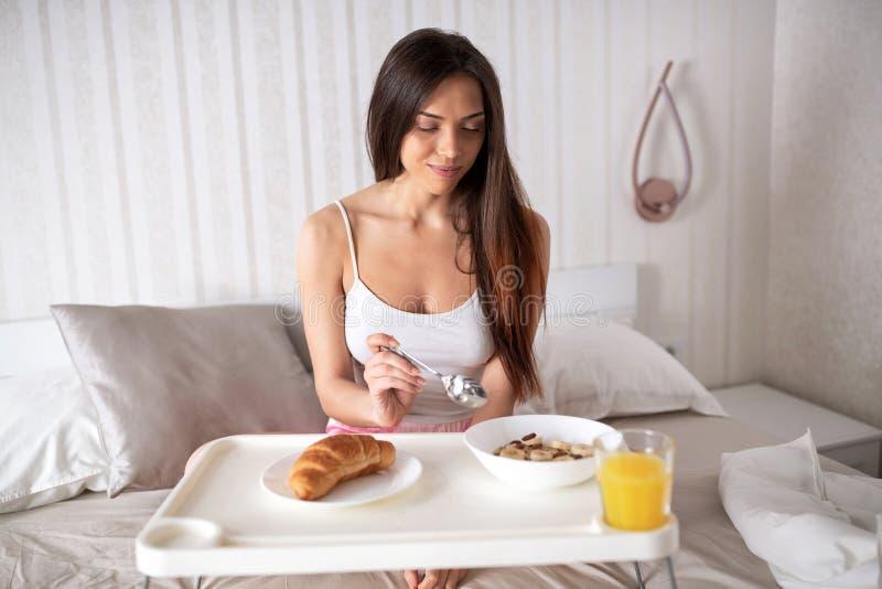 Süße Studentin, die Frühstück im Bett isst lizenzfreie stockbilder