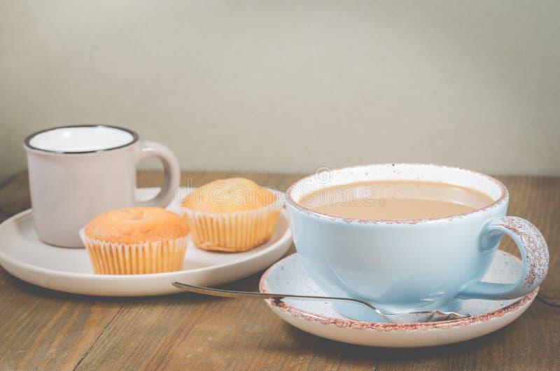 Süßes Hörnchen und ein Tasse Kaffee im Hintergrund Muffins und blauer Becher mit Cappuccino und Creme in einer kleinen Schale zum stockfotografie