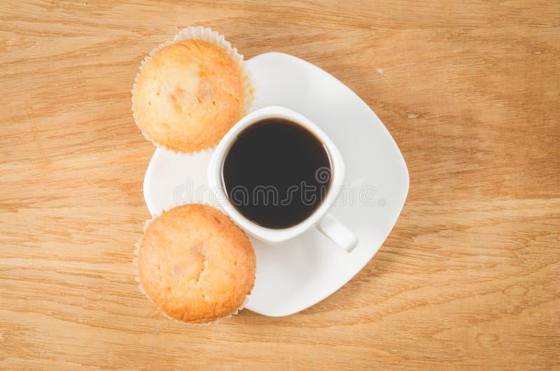 Süßes Hörnchen und ein Tasse Kaffee im Hintergrund Weiße Schale des heißen schwarzen Kaffees und zwei Muffins, Draufsicht Tasse K stockfoto