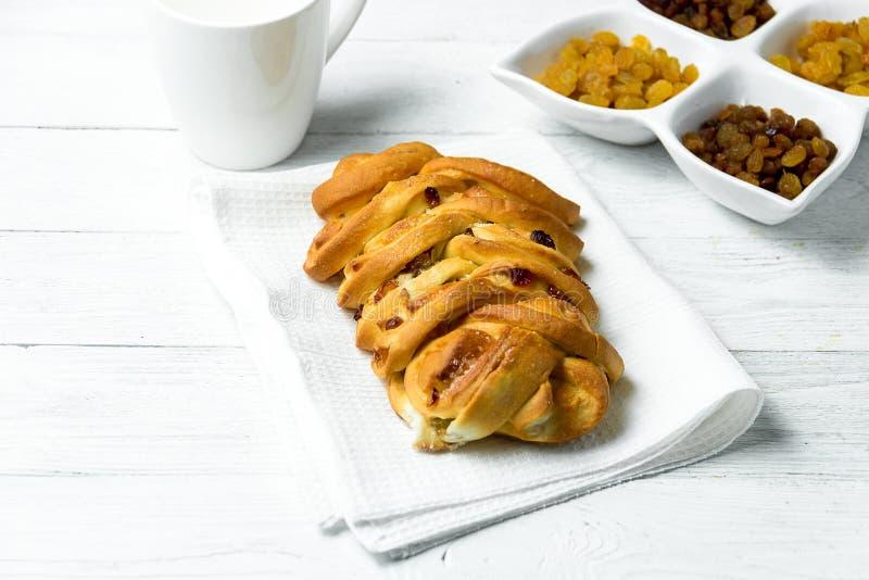 Süßes umsponnenes Brot mit Rosinen auf Geschirrtuch auf weißem hölzernem Hintergrund stockbilder