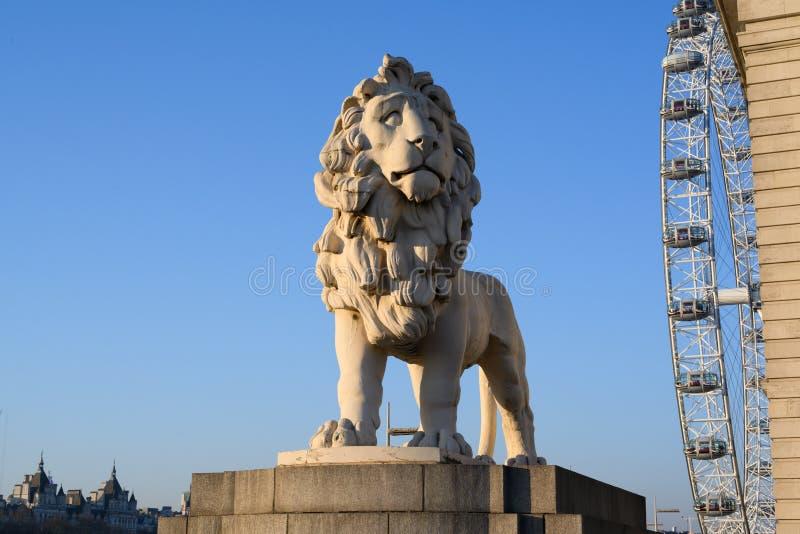 Südufer-Löwe Löweskulptur, welche die Westminster-Brücke, London, Großbritannien schützt lizenzfreies stockfoto