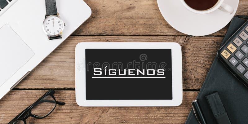 SÃguenos, testo spagnolo per Follow noi sullo schermo del comput della compressa immagine stock libera da diritti
