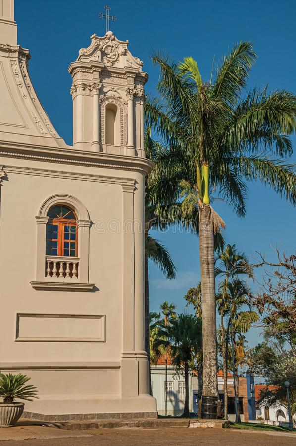 Detail of church corner and palm tree in front of a cobblestone square at São Manuel. stock photo