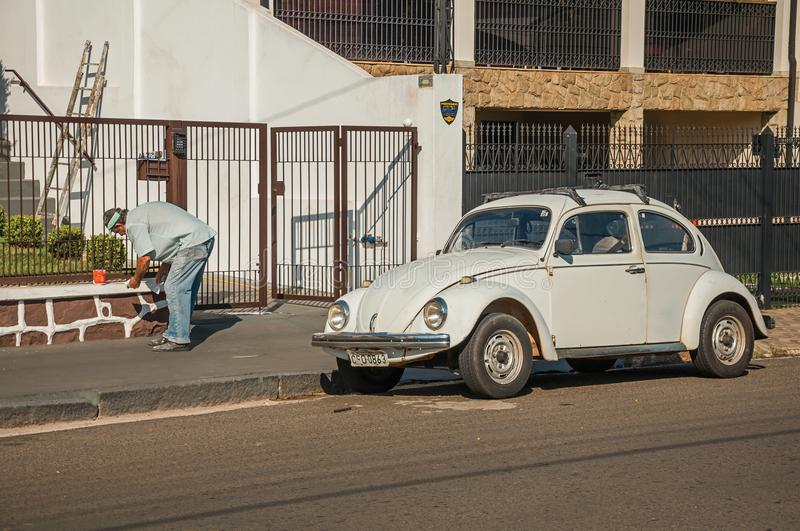 Man painting fence in front of house with a Beetle car parked next to it at São Manuel. São Manuel, southeast Brazil - October 14, 2017. Man painting royalty free stock photo