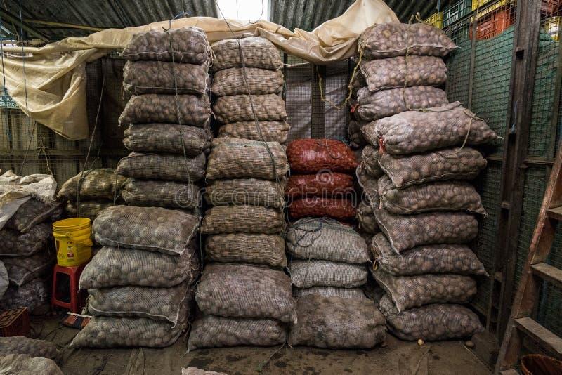 Säckar av potatisar på Paloqumao marknadsBogotà ¡, arkivbild