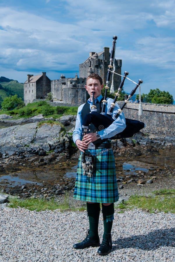 Säckpipe- spelare framme av berömda Eilean Donan Castle i högländerna av Skottland arkivfoto