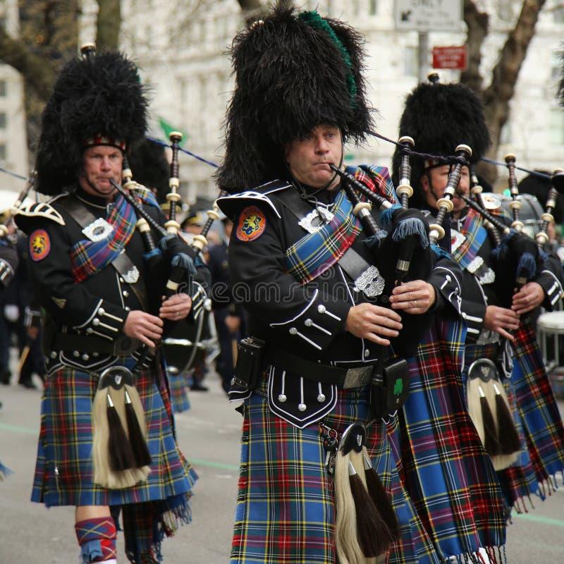 Säckpipeblåsare av den Nassau polisen leda i rör, och valsar som marscherar på Stets Patrick dag, ståtar royaltyfria bilder