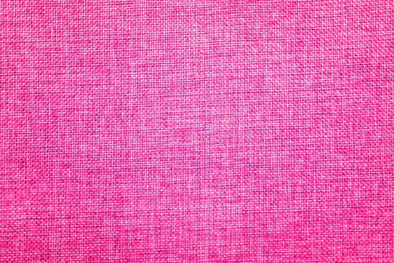 Säckvävbakgrund som färgas i rosa och vit blandning arkivfoto
